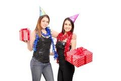 Dos amigos femeninos jovenes que colocan juntos holdinggifts cercanos en Imágenes de archivo libres de regalías