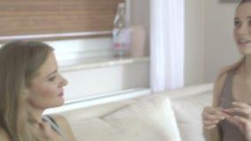 Dos amigos femeninos jovenes que se sientan en el sofá en la sala de estar en casa almacen de video