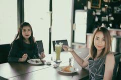 Dos amigos femeninos jovenes ríen y almorzando juntos en descanso Fotografía de archivo