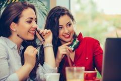 Dos amigos femeninos que compran en línea con la tarjeta de crédito y un ordenador portátil que se sienta en el café imagen de archivo