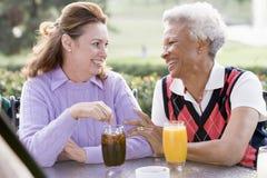 Dos amigos femeninos que gozan de una bebida por un golf C fotos de archivo