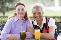 Dos amigos femeninos que gozan de una bebida por un golf C Fotografía de archivo