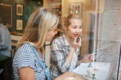 Dos amigos femeninos que se sientan dentro del café que habla y que come el café fotografía de archivo