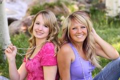 Dos amigos femeninos que se sientan junto Foto de archivo libre de regalías