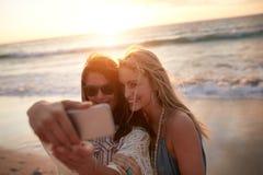 Dos amigos femeninos que toman un selfie en la playa Imágenes de archivo libres de regalías