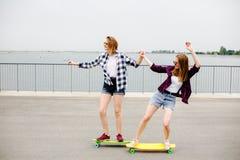 Dos amigos femeninos sonrientes que aprenden longboard que monta con la ayuda Concepto de la amistad foto de archivo
