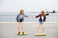 Dos amigos femeninos sonrientes que aprenden longboard que monta con la ayuda Concepto de la amistad foto de archivo libre de regalías