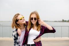 Dos amigos femeninos sonrientes que se abrazan en la calle Concepto de los días de fiesta, de las vacaciones, del amor y de la am foto de archivo libre de regalías