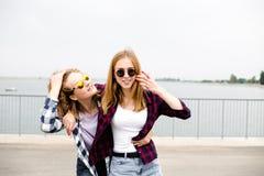 Dos amigos femeninos sonrientes que se abrazan en la calle Concepto de los días de fiesta, de las vacaciones, del amor y de la am foto de archivo