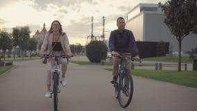 Dos amigos hombre y mujer están conduciendo las bicis en ciudad por la tarde, hablando juntos almacen de metraje de vídeo