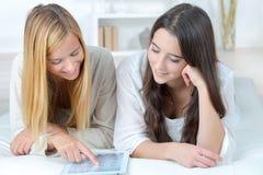 Dos amigos jovenes adolescentes que usan la tableta del ordenador Fotografía de archivo libre de regalías