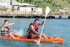 Dos amigos jovenes ejoying las vacaciones, entrando en el mar con la canoa amarilla Foto de archivo