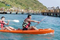 Dos amigos jovenes ejoying las vacaciones, entrando en el mar con la canoa amarilla Imagen de archivo