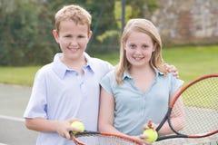 Dos amigos jovenes en la sonrisa del campo de tenis Fotos de archivo libres de regalías