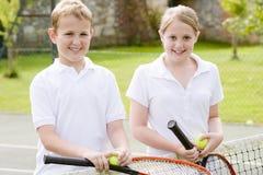 Dos amigos jovenes en la sonrisa del campo de tenis Fotos de archivo