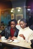 Dos amigos jovenes que almuerzan común en restaurante durante la rotura de trabajo, estudiantes que se relajan en café después de Fotos de archivo