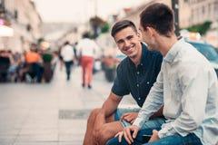 Dos amigos jovenes que hablan junto en una calle de la ciudad Imagen de archivo libre de regalías