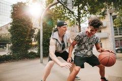 Dos amigos jovenes que juegan a baloncesto en corte al aire libre Foto de archivo