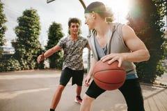 Dos amigos jovenes que juegan a baloncesto en corte al aire libre Imagen de archivo libre de regalías