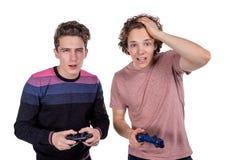 Dos amigos jovenes que juegan a los videojuegos y que llevan a cabo gamepads Concepto del torneo o del torneo foto de archivo