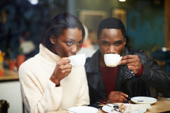 Dos amigos jovenes que sostienen las tazas beben el café en café Foto de archivo libre de regalías