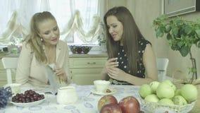 Dos amigos jovenes sonrientes atractivos que tienen tiempo relajante en la mesa de comedor almacen de video