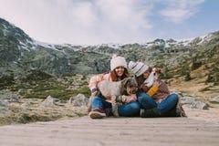 Dos amigos juegan con sus perros que se sientan en el prado con una montaña grande detrás de ellos fotos de archivo libres de regalías