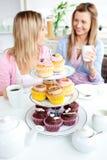 Dos amigos lindos que comen las magdalenas en la cocina Imagen de archivo libre de regalías