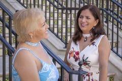 Dos amigos maduros de las mujeres paran la charla en la parte inferior de las escaleras imagen de archivo libre de regalías
