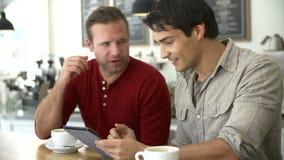 Dos amigos masculinos en la cafetería que mira la tableta de Digitaces almacen de video