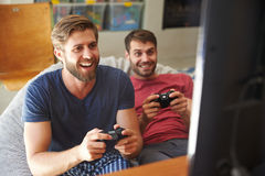 Dos amigos masculinos en los pijamas que juegan al videojuego junto Imagen de archivo