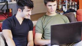 Dos amigos masculinos jovenes que usan el ordenador portátil Imagen de archivo libre de regalías