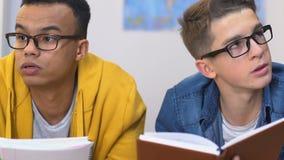 Dos amigos masculinos que cuentan en la cabeza, haciendo la preparación junta, concepto de la educación almacen de metraje de vídeo
