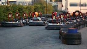 Dos amigos masculinos que disfrutan de paseo en el circuito del kart, divirtiéndose junto, competencia metrajes