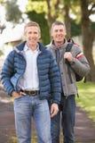 Dos amigos masculinos que recorren al aire libre en parque del otoño Fotos de archivo libres de regalías