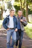 Dos amigos masculinos que recorren al aire libre en parque del otoño Imagen de archivo