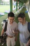 Dos amigos masculinos que sonríen y que consiguen listos para salir del campo de golf, mirando abajo el teléfono Imagen de archivo libre de regalías
