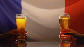 Dos amigos masculinos que sostienen los vidrios de cerveza, bandera francesa en el fondo, aficionados deportivos almacen de video