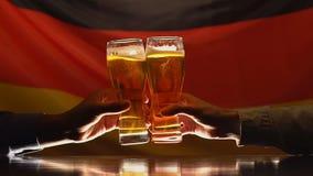 Dos amigos masculinos que tintinean los vasos de cerveza, bandera alemana en el fondo, resto del pub metrajes