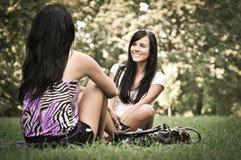 Dos amigos - muchachas que hablan afuera Foto de archivo libre de regalías