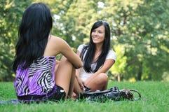 Dos amigos - muchachas que hablan afuera en parque Imagenes de archivo
