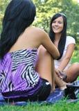 Dos amigos - mujeres que hablan al aire libre en parque Foto de archivo libre de regalías