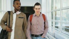 Dos amigos multi-étnicos hermosos jovenes que caminan abajo del pasillo vidrioso blanco en el paso que habla de la universidad co almacen de video
