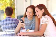 Dos amigos o familias que comparten un teléfono elegante en una cafetería