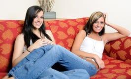 Dos amigos o hermanas femeninos se relajan en el sofá Foto de archivo