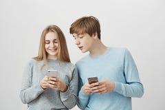 Dos amigos positivos que corrigen el selfie al post-it en red social Pares cariñosos amistosos, novia que muestra al novio Imagen de archivo libre de regalías