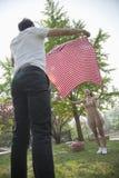 Dos amigos que abren una manta a cuadros y que consiguen listos para tener una comida campestre en el parque Imagenes de archivo