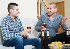 Dos amigos que beben la cerveza en casa Foto de archivo