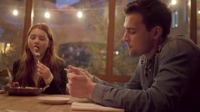 Dos amigos que comen en el café moderno que se sienta cerca de la ventana La mujer joven con el pelo rojo come la comida de la pl metrajes