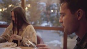 Dos amigos que comen en el café moderno que se sienta cerca de la ventana La mujer joven con el pelo rojo come la comida de la pl almacen de metraje de vídeo
